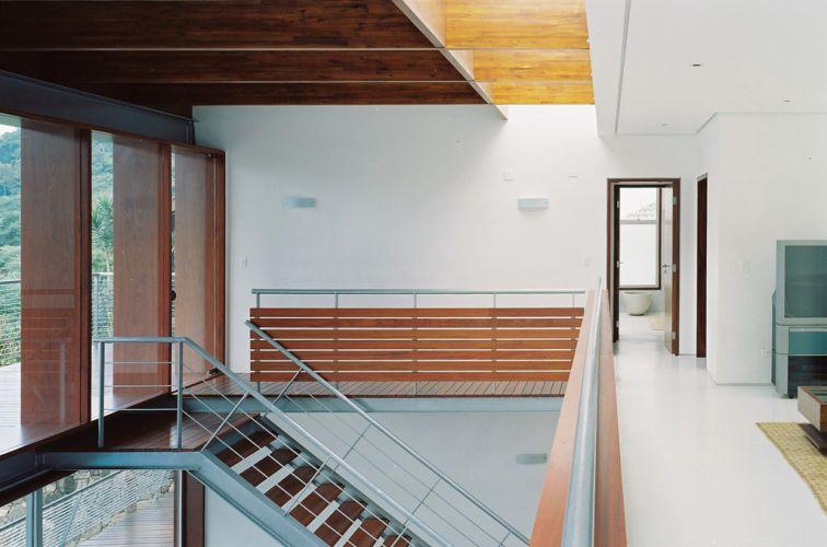 No piso superior da casa em São Sebastião, de Biselli Katchborian Arquitetos, grandes painéis fixos de vidro levam luz natural aos ambientes, ligados por escada metálica ao núcleo da casa: o estar, no piso térreo.