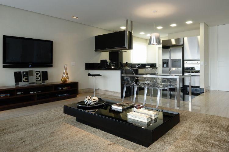 O living integrado com a cozinha funciona como uma sala íntima. Ao centro, mesa de madeira com tampo de vidro da Artefacto e, sob a TV, o móvel de madeira acomoda livros e equipamentos. Ao fundo, a cozinha da Formaplas, iluminada com plafons