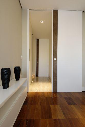 Para preservar a ala íntima, foram criados outros painéis como este, que fecha o escritório para se transformar em quarto de hóspedes, revestido em laca e com puxador de couro, desenhados pelo escritório com execução da Grifel Marcenaria