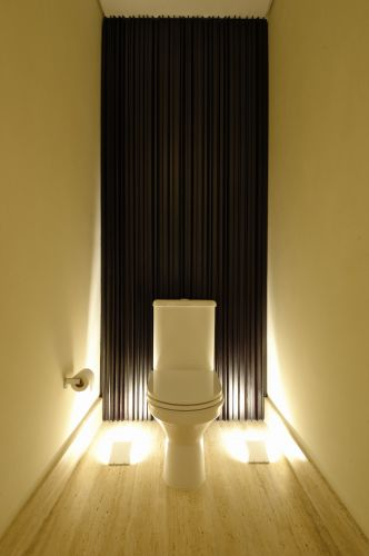No lavabo superior, atrás da bacia, foi instalado um painel de madeira ebanizada preta