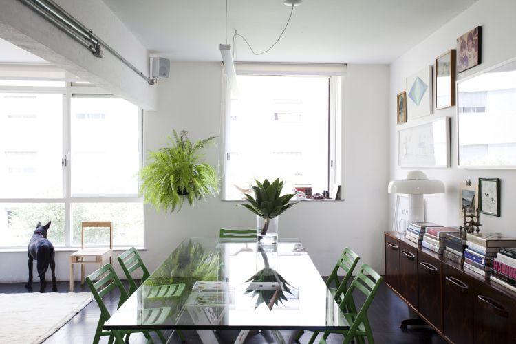 Na sala de jantar, mesa House of Cards, também desenhada por Mauricio Arruda, e cadeiras verdes dobráveis Air, da Tom Dixon. Na parede, mais memórias: obras de brasileiros (Marepe, Barsotti e Ernesto Neto), além de fotos da infância