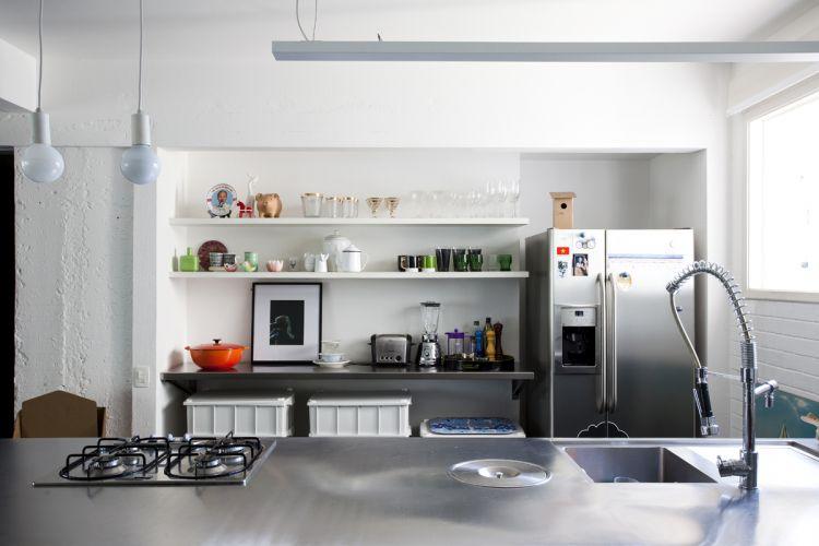A bancada da cozinha é de marcenaria, executada pela Yamato; tampo, prateleira e geladeira são de aço inox