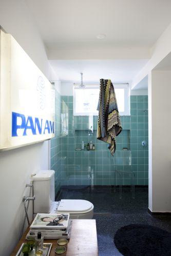Para iluminar o banheiro principal da suíte, letreiro da extinta companhia aérea Pan Am, comprado num depósito na periferia de São Paulo