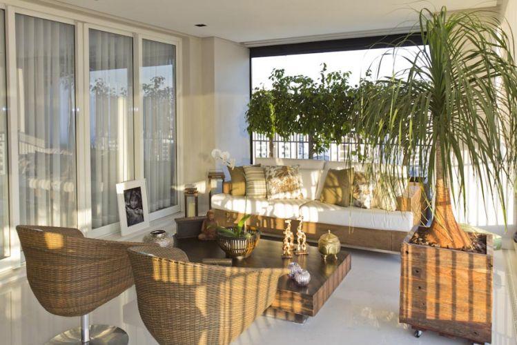 A varanda gourmet é continuação da sala de estar: o verde das plantas mistura-se aos móveis de madeira de demolição da Amazônia Móveis, e às cadeiras giratórias de fibra, da Artefacto