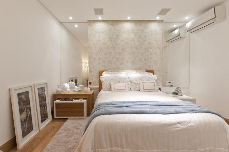 As peças de decoração se combinam em volumetria assimétrica, corrigida com espelhos e pela persiana, decorada como um papel de parede, instalada atrás da cama