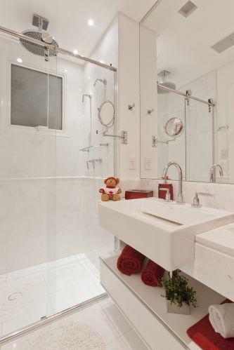 Neste banheiro criado por Mayra Lopes para um apartamento em São Paulo predomina o branco, com toques de vermelho. A cerâmica foi aplicada até meia-parede; o chuveiro é Deca