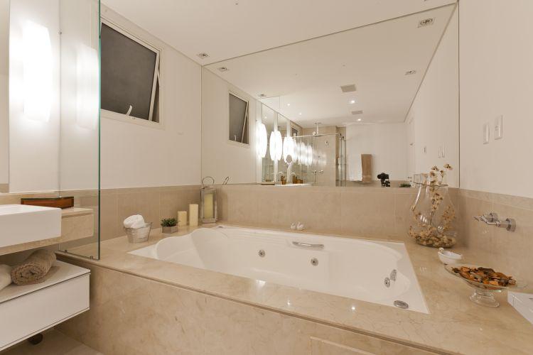 O projeto de Mayra Lopes previu a colocação de espelho em uma das paredes do banheiro, para fazê-lo parecer maior. Os revestimentos são porcelanato e mármore do tipo travertino esculpido e o mobiliário é da Segatto. Ducha quadrada da Deca