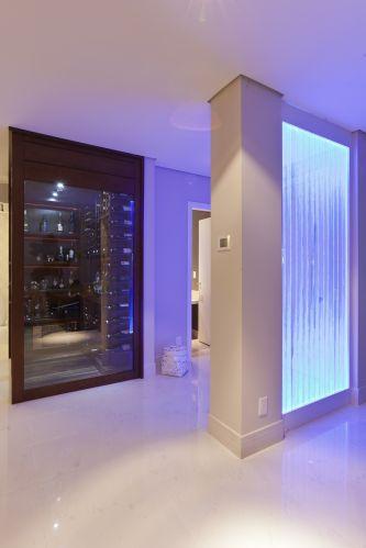 À entrada, painel de acrílico com bolhas de água (da Mondiale Acrílicos), que muda de cor a partir do branco, passando por lilás, verde, azul e vermelho, separa home theather do lavabo. Projeto de interiores de Mayra Lopes