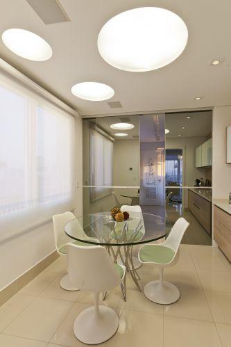 A copa é separada da cozinha por porta de espelho fumê, da Segatto, com tratamento acústico para garantir privacidade nos cafés da manhã; a mesa é da Artefacto