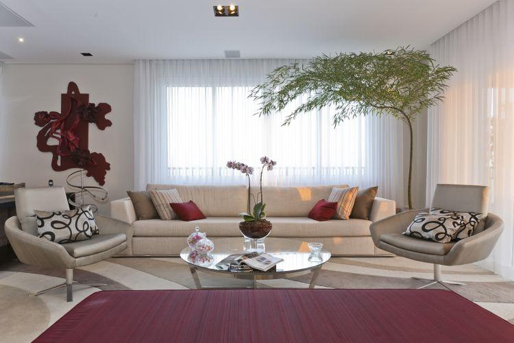 Sofá com revestimento de linho e mesa de centro redonda, de vidro, da Breton Actual; o puff vermelho é da Artefacto