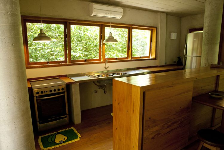 No extremo oposto ao quarto, está a cozinha delimitada pelo balcão em madeira. Janelas do tipo máximo-ar controlam a ventilação natural na Casa nas Árvores, projetada por George Mills