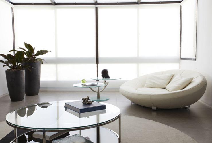 A nova sala de estar do apartamento dúplex reformado pela arquiteta Monica Drucker anexou um pequeno terraço protegido por tela de enrolar da Luxaflex, e foi ambientada com chaise redonda forrada com couro branco da designer suíça Jane Worthington, e mesa desenhada por Peter Draenert (Staaten), sobre a qual se encontra uma cabeça preta