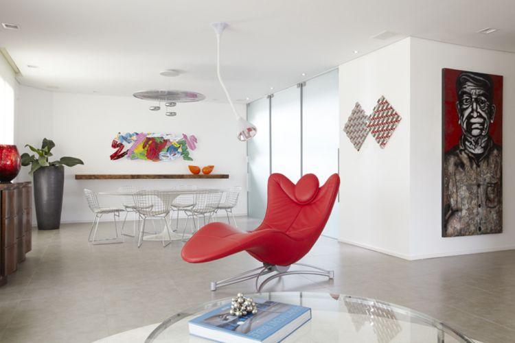 Reformado pela arquiteta Monica Drucker, o apartamento de 600 m² na zona este de São Paulo teve sua área social integrada. Ao fundo, a sala de jantar e, em primeiro plano, a chaise forrada de couro vermelho, modelo criado pela designer suíça Jane Worthington, iluminada pela luminária Pipe (La Lampe), desenhada pelos arquitetos Herzog e de Meuron