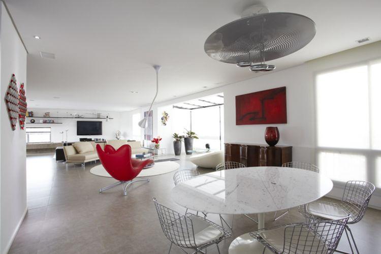 Vista geral da maior parte dos ambientes sociais do apartamento dúplex de 600 m², reformado pela arquiteta Monica Drucker, na zona oeste da capital. Predominam as paredes brancas e móveis e luminárias de desenho contemporâneo nas cores branco, vermelho e preto