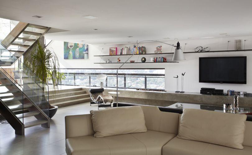 Em primeiro plano, sofá da alemã Rolf Benz. Ao fundo, o home theatre, onde a bancada com lareira a gás em concreto (executada pela Dalle Piage), ocupa toda a extensão da parede. Na parede, prateleiras Carrapixo, da Dpot. A chaise Le Corbusier e mesinha Saarinen ficam no espaço de transição entre o home theatre e o terraço coberto