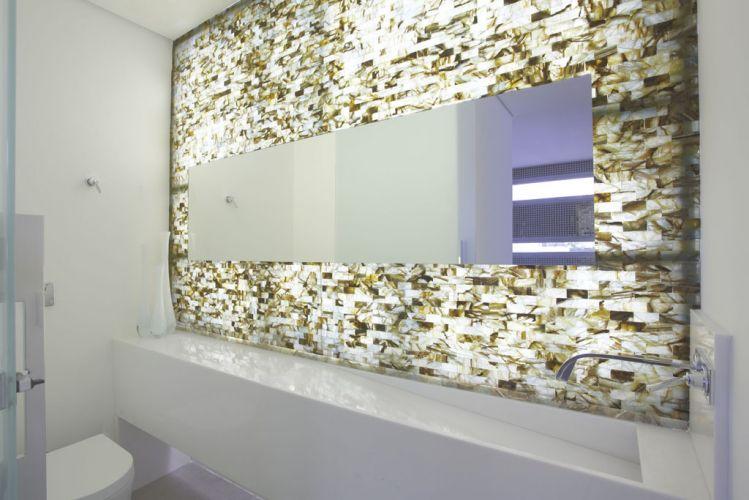 No lavabo, painel de pedras ônix iluminado por lâmpadas fluorescentes, e bancada em mármore, com metais e louças Deca. Projeto da arquiteta Monica Drucker