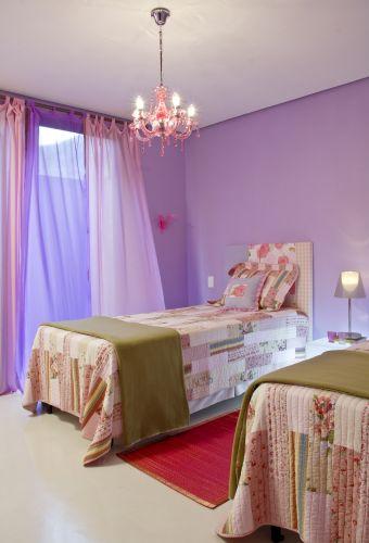 No quarto das meninas, uma proposta em rosa e lilás. Retalhos de patchwork decoram o painel da cabeceira, feito pela própria decoradora com uma prancha de MDF coberta por manta acrílica, e a ajuda de um grampeador de tapeceiro. A colcha de matelassê em patchwork e o tapete de tear são da Cinerama. A cortina lilás é um sári indiano, a rosa, é um voil. O lustre de cristais é da Urban e a parede foi pintada com tinta Lukscolor, referência LKS 704