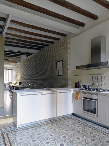 A pedido de Welsh, dois charmosos elementos catalães foram mantidos e restaurados em seu loft barcelonês: os mosaicos geométricos que compõem o chão da cozinha e as vigas de madeira exposta que recuperaram sua cor mel