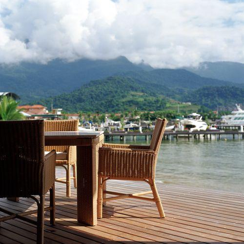 Na varanda, que é totalmente integrado ao living, deck de madeira e móveis de fibra sintética de Armando Cerello