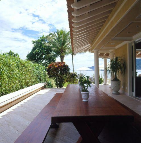 Mesa e banco de madeira de Minas Gerais, colocados na varanda junto à sala de jantar, são utilizados para os almoços em família