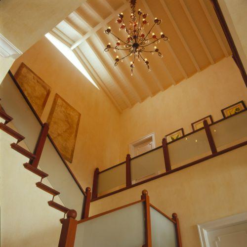 Outro ângulo da escada de onde é possível observar o teto com vigas e lambris do telhado pintados de branco. A abertura protegida por vidro permite a passagem de luz natural, que ilumina todo o vão da escada