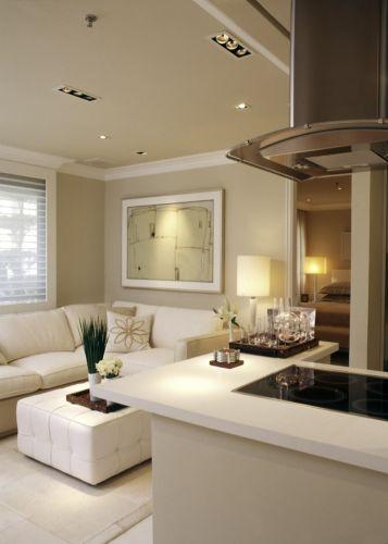 A foto mostra o estar, a cozinha americana e, ao fundo, a porta de acesso à suíte principal. A combinação de tonalidades neutras confere sofisticação ao conjunto