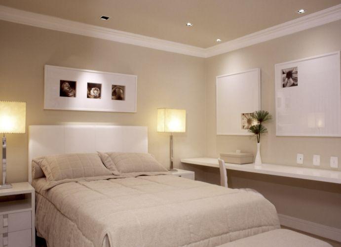 Na suíte principal repetem-se os tons neutros usados nas outras áreas do apartamento. As mesas laterais de madeira com acabamento de laca branca foram desenhadas pelo arquiteto. Na parede lateral, uma bancada de trabalho