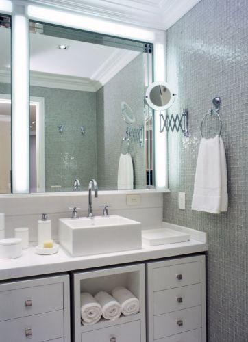 No banheiro do casal, paredes revestidas com mosaico de vidro da Vidrotil, tampo da bancada e piso em mármore branco Thassus e louças da Deca. Bastante práticos, os gabinetes sob a bancada, desenhados por Oscar Mikail, podem ser facilmente deslocados graças à utilização de rodízios