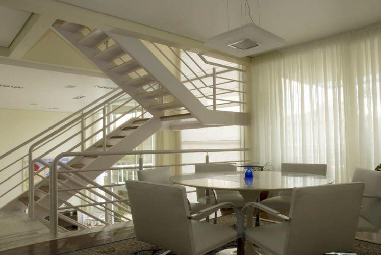 Do outro lado da escada, a sala de jantar tem a mesa Saarinen, desenho de Eero Saarinen, cadeiras Brno, outro clássico de Mies van der Rohe, e persianas de dobrar da Uniflex