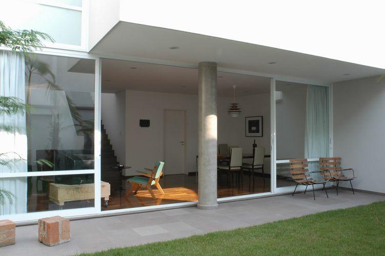 Vista da varanda da sala coberta pelo volume do pavimento superior, sustentado pelo pilar de concreto aparente
