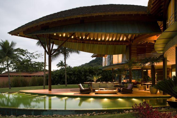 Com projeto assinado pelo escritório Mairenes Patalano, esta piscina de concreto armado atravessa a casa como um rio, transformando-se em espelho d'água na varanda, onde é berço de plantas aquáticas. Revestida com mosaico Vidrotil em tons de verde, tem borda infinita que a faz ligação com o mar de Angra dos Reis