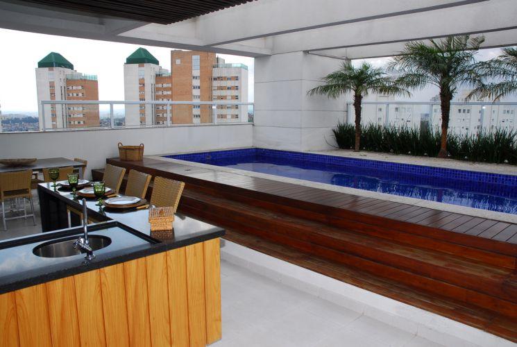 A piscina desta cobertura, executada com concreto, já fazia parte do projeto original da construtora. A designer Paula Gambier responsabilizou-se pela escolha do revestimento em pastilha para piscinas da Eliane, e pelo deck de ipê acabado com polietileno