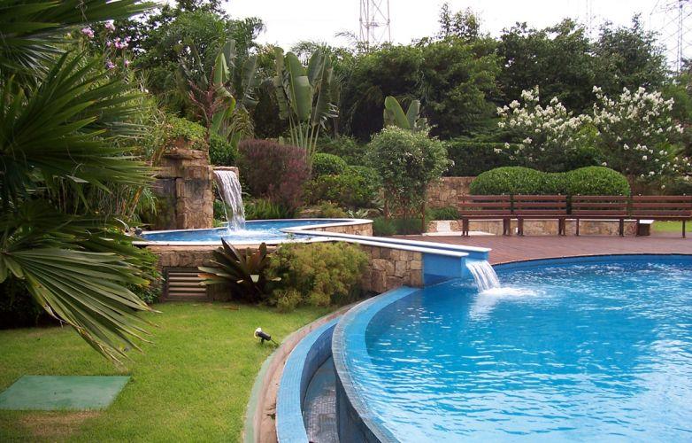 O paisagismo, assinado por Rodolfo Geiser, contemplou também a piscina integrada ao jardim. Feita de alvenaria revestida de pastilhas de vidro, tem borda infinita e piso de pedra São Tomé e deck de madeira. A piscina infantil foi posicionada para formar uma cascata