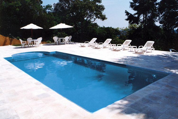 Instalada pela Planeta Água, esta piscina de fibra de vidro com prainha recebeu externamente piso de pedra