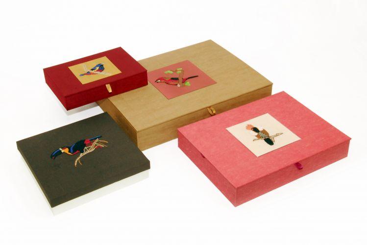 Da Safira Sedas, as caixas revestidas com tecidos Gustaviano de várias cores (seda com linho), tem dimensões que vão 20 cm de largura a 41 cm de largura. Preço: R$ 270 (pequena); R$ 570 (média); R$ 630 (grande)www.safirasedas.com.brPreços consultados em abril de 2011 e sujeitos a alterações