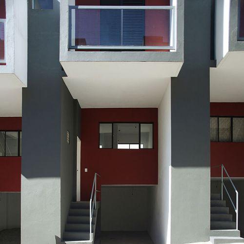 A garagem com vaga para um carro e ainda um depósito elevam o pavimento do ambiente de estar do nível da rua. O quarto da frente, no piso superior, possui varanda com guarda-corpo de vidro