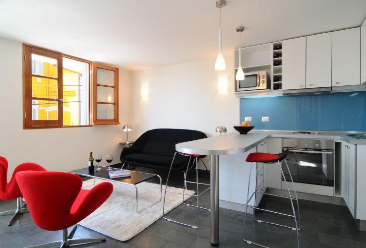 O espaço integrado, característico dos lofts, pode ser bem visualizado na comunhão entre a sala de estar e a cozinha americana. O revestimento azul vitrificado quebra a monotonia das peças bancas que compõem os armários da cozinha. Na sala, móveis de design são arejados pela janela de esquadria em madeira e abertura total