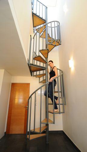 O pé direito altíssimo é preenchido pela escada caracol com degraus em madeira. O modelo economiza espaço e dá charme para o acesso ao mezanino e ao piso mais alto do loft triplex