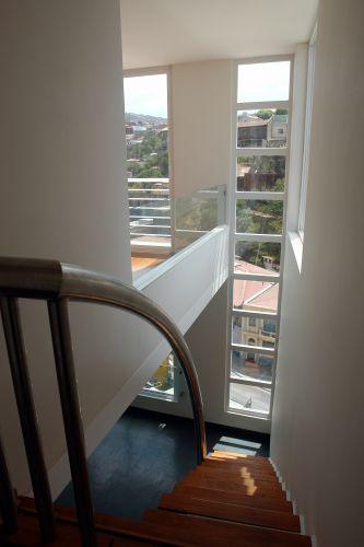 Loft triplex tem a escada de madeira aplicada à parede e guarda-corpo de vidro no mezanino. As janelas de vinil (PVC) são amplas e garantem luz farta aos ambientes
