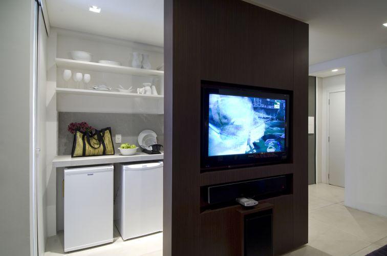 O branco que predomina nas paredes, piso e móveis faz sobressair o amadeirado do móvel da TV