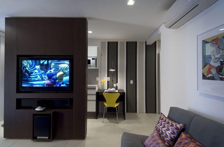 O tom amadeirado da folha de nogueira linheiro aplicada ao móvel de MDF (onde a TV e o home theater estão embutidos) confere o ar masculino ao ambiente, reforçado pelos tons de cinza do revestimento do sofá e das listras pintadas na parede