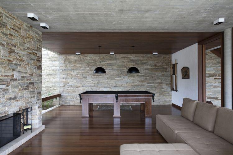 Ao lado da entrada social, no piso inferior, o amplo espaço de jogos. O concreto aparente foi deixado em parte do teto, no espaço destinado ao estar, com lareira e televisão. No piso e parte do forro foi usado assoalho de madeira cumaru, e nas paredes, pedras são tomé. Sobre a mesa de jogos, luminárias da Lumini