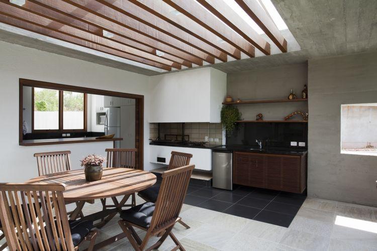 A churrasqueira está integrada à cozinha. Uma grande pérgula protegida por vidro permite a entrada de luz natural sobre o ambiente