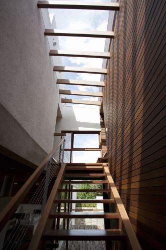 Pérgula de madeira e vidro implantada sobre a escada leva luz ao interior. Fechamentos em vidro propiciam a integração do interior com o entorno verde