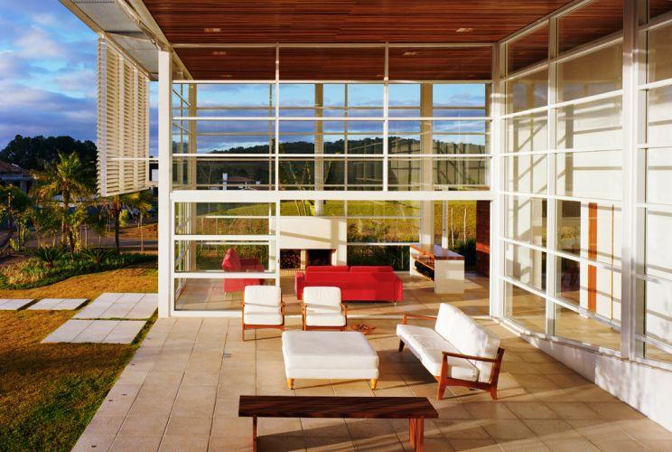 A caixilharia e os vidros permitem uma quase total integração da varanda ao estar com lareira. O revestimento cimentício da Solarium aplicado no piso dos dois ambientes reforçam a continuidade