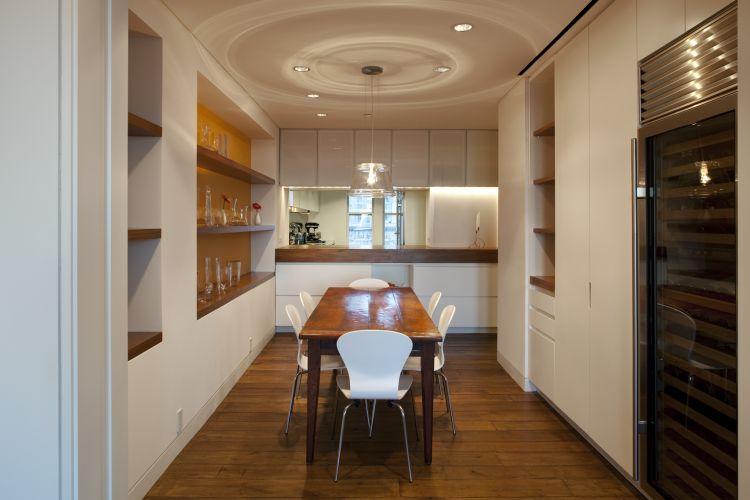 Vista da copa mostra, ao fundo, o passa-prato com armário separa o ambiente da cozinha