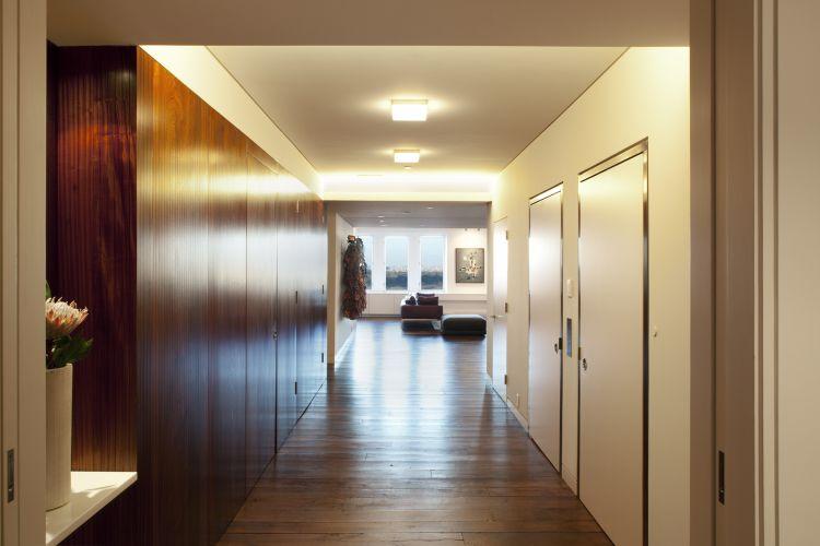 Com a reforma,o hall de distribuição do andar foi incorporado ao apartamento. O espaço recebeu revestimento de painéis de madeira para ocultar as instalações do edifício e faz a articulação entre a área social, na face norte do apartamento, e os ambientes voltados para o sul