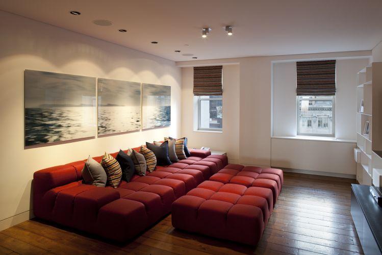 A sala de TV com sofá e pufes vermelhos, e cortinas de enrolar listradas no mesmo padrão das almofadas é um ambiente mais acolhedor