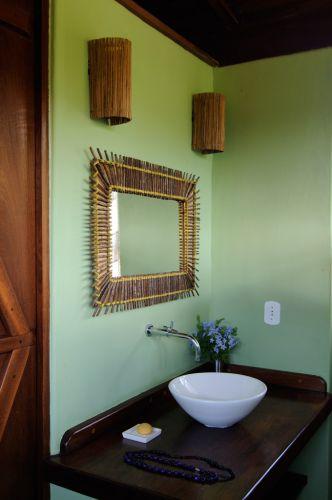 Louças e metais minimalistas, luminárias e objetos artesanais e cores vibrantes são os elementos marcantes de um dos banheiros da casa em Trancoso (BA)
