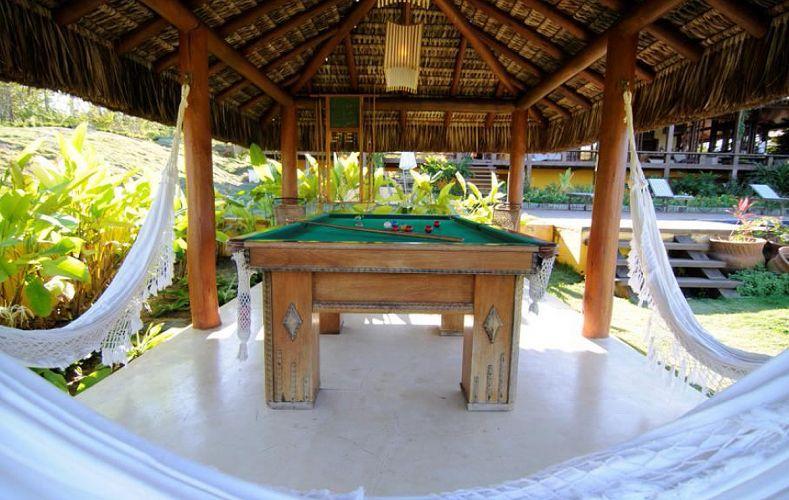Em meio ao jardim, área une diversão e descanso com mesa de sinuca e redário cobertos por sapê